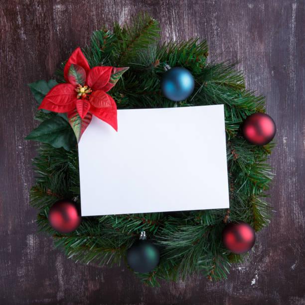 weihnachtskranz mit dekorationen und leerem weißem papierblatt auf holzhintergrund.  neujahrsdekoration. obere ansicht, kopierbereich. - weihnachtssterne aus papier stock-fotos und bilder