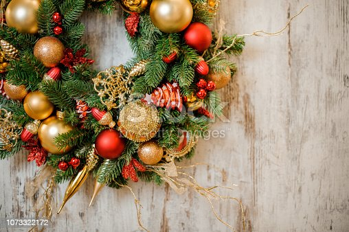istock Christmas wreath with golden and red decoration 1073322172