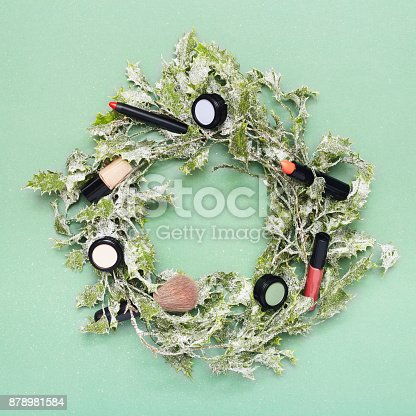 istock Christmas wreath with makeup on green background 878981584