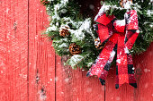 A Christmas wreath made from evergreens, pine cones and a red & black plaid bow, hanging on a red barn while it is snowing.