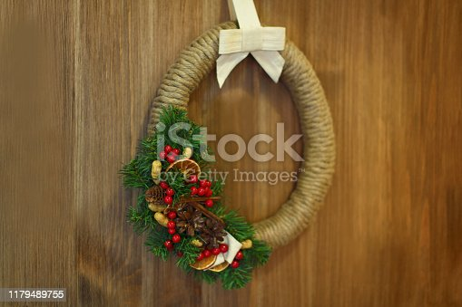 909924232 istock photo Christmas wreath with spruce and toys hanging on the brown door 1179489755