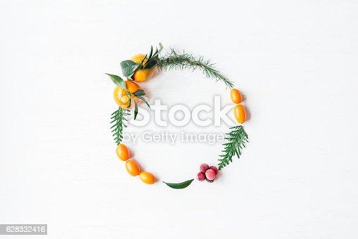 istock Christmas wreath with tangerines, cranberries, thuja branches, kumquats 628332416