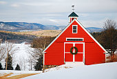 A Christmas wreath hangs on a red barn in a snowy mountain setting in New England