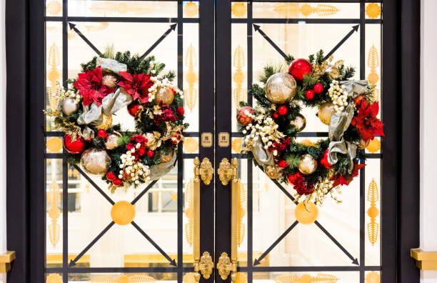 weihnachtskränze auf glastür - deko hauseingang weihnachten stock-fotos und bilder