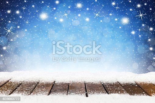 christmas xmas background with wooden snowy planks in front of blue night sky with stars and snowflakes