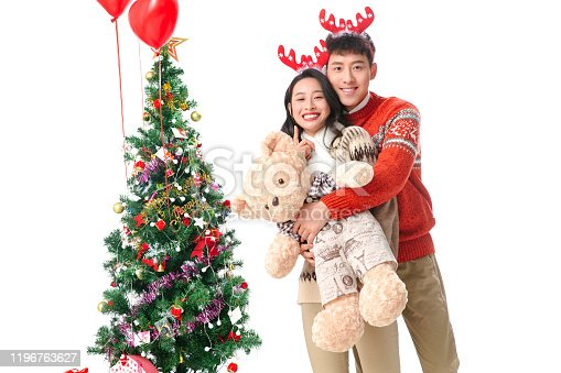 Christmas young couple holding a teddy bear