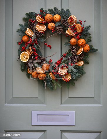 Traditional Decorative Yule Christmas wreath on a Victorian Front with period (19th century) knocker and letter box door in London, UK