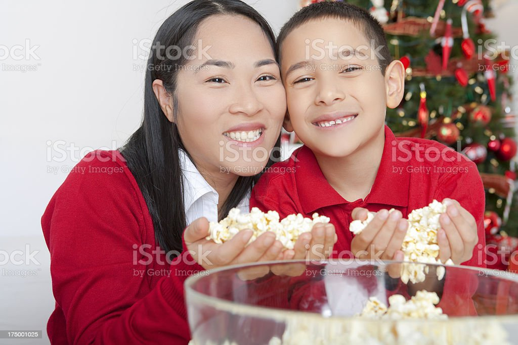Christmas-Asian mother and son stringing popcorn royalty-free stock photo