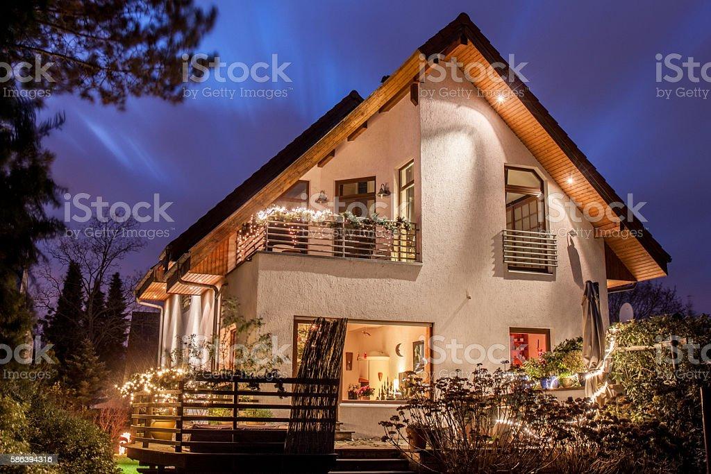 Weihnachtlich beleuchtetes Haus am Abend vor ziehenden Wolken stock photo
