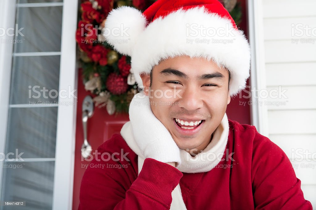 Christmas-Smiling asian man sitting on his door steps royalty-free stock photo