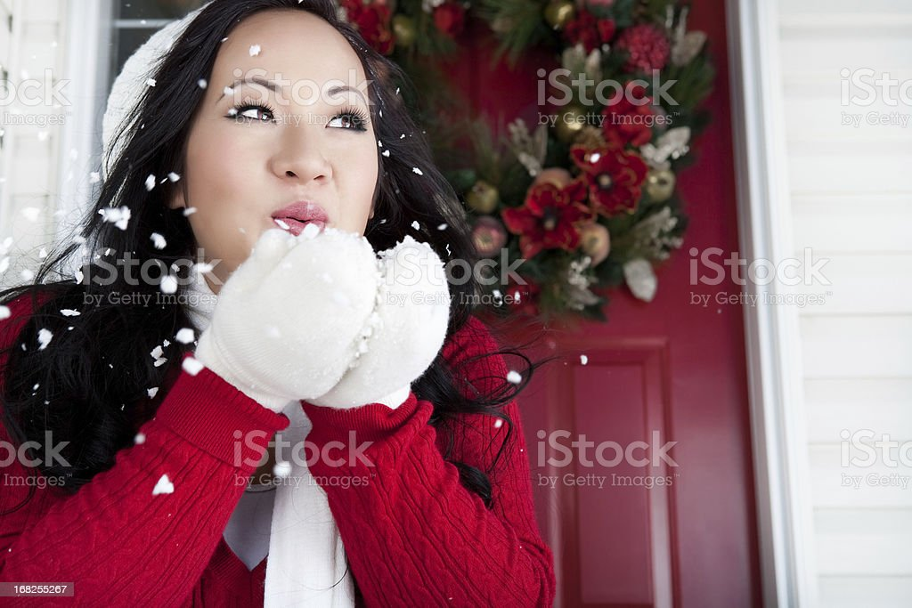 Christmas-Smiling asian woman blowing snow royalty-free stock photo