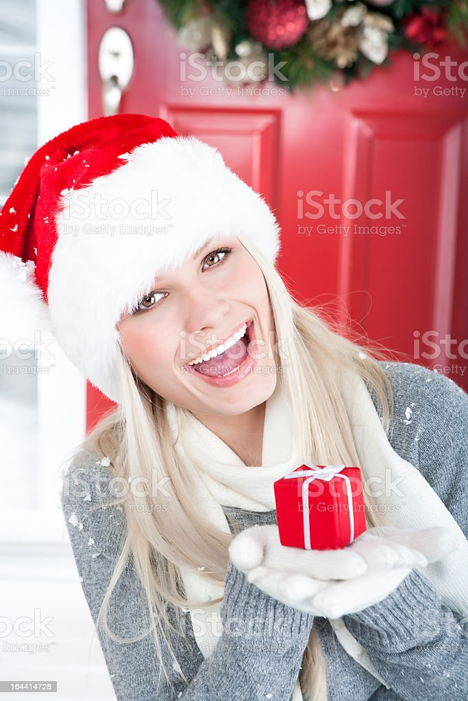 Christmas-Smiling woman holding red present royalty-free stock photo