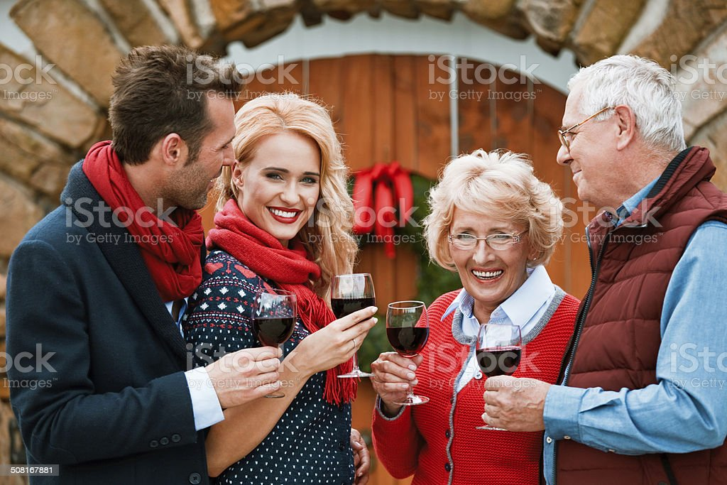 Christmast toast Outdoor portrait of happy mature parents toasting with red wine with their adult children against doors decorated with christmast wreath.  Active Seniors Stock Photo