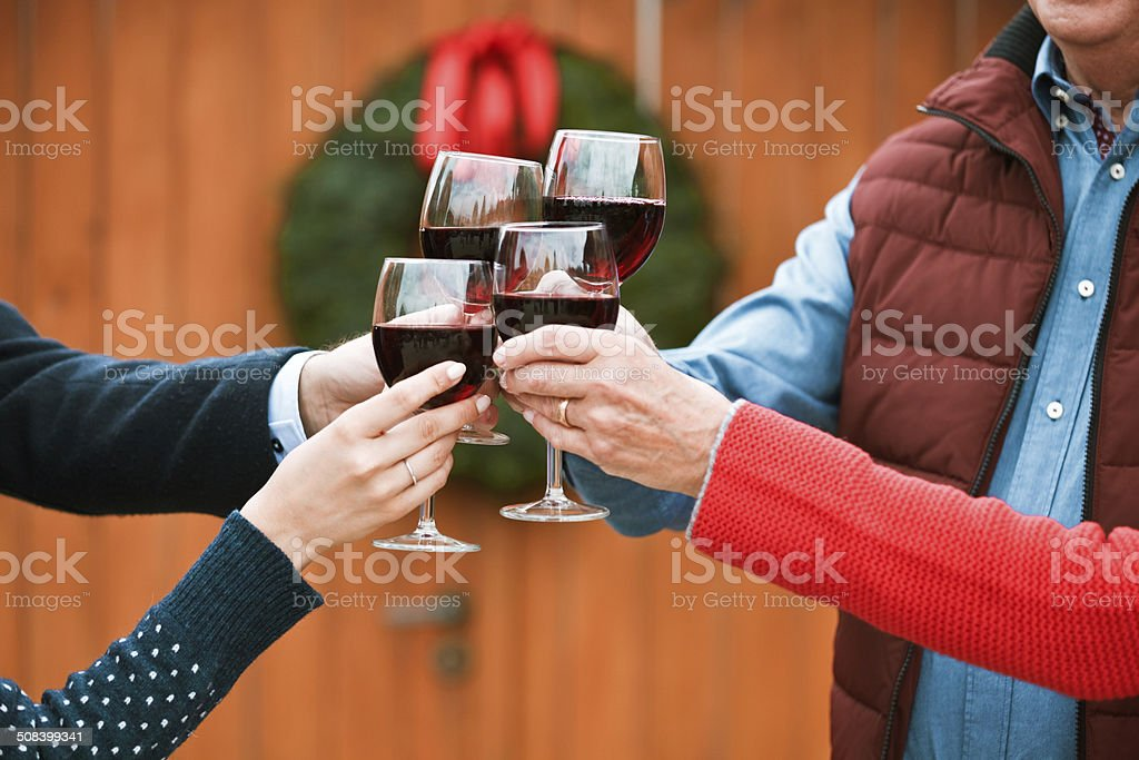 Christmast toast Four people toasting with red wine against doors decorated with christmast wreath. Close up of wine glasses. Adult Stock Photo