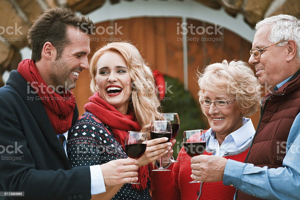 Christmast toast Outdoor portrait of happy family toasting with red wine against doors decorated with christmast wreath.  Active Seniors Stock Photo