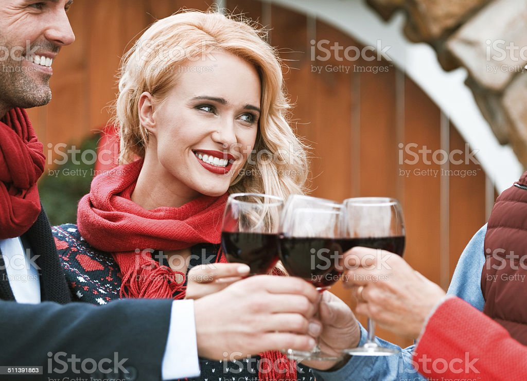 Christmast toast Outdoor portrait of happy family toasting with red wine against doors decorated with christmast wreath. Focus on beautiful blonde. Active Seniors Stock Photo