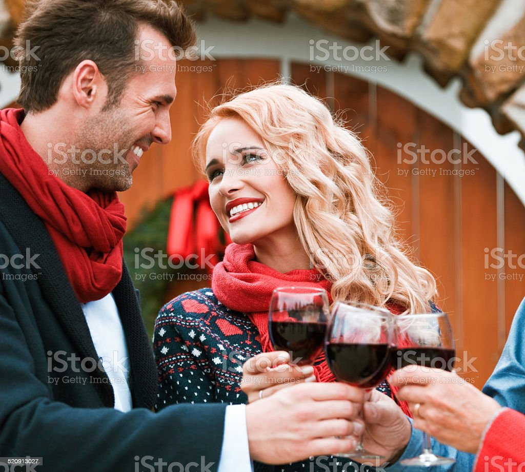 Christmast toast Outdoor portrait of happy couple toasting with red wine against doors decorated with christmast wreath.  Adult Stock Photo