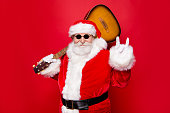 Christmastime December concept. Aged fancy stylish grandfather Nicholas in costume white beard show rock n roll sign hold guitar on shoulder ready playing song sound isolated on red background