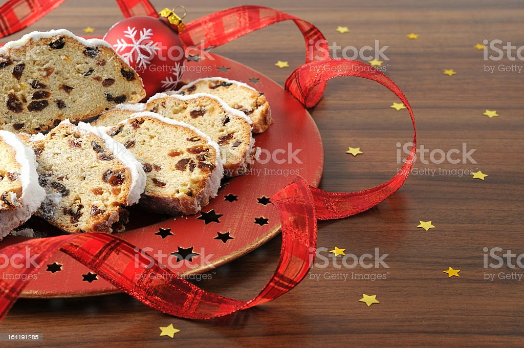 christstollen on red plate with star shape ornaments - Stollen stock photo