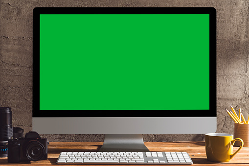 Chroma key green screen computer with photography equipment on table. Table top shot of interior space with window light effect.