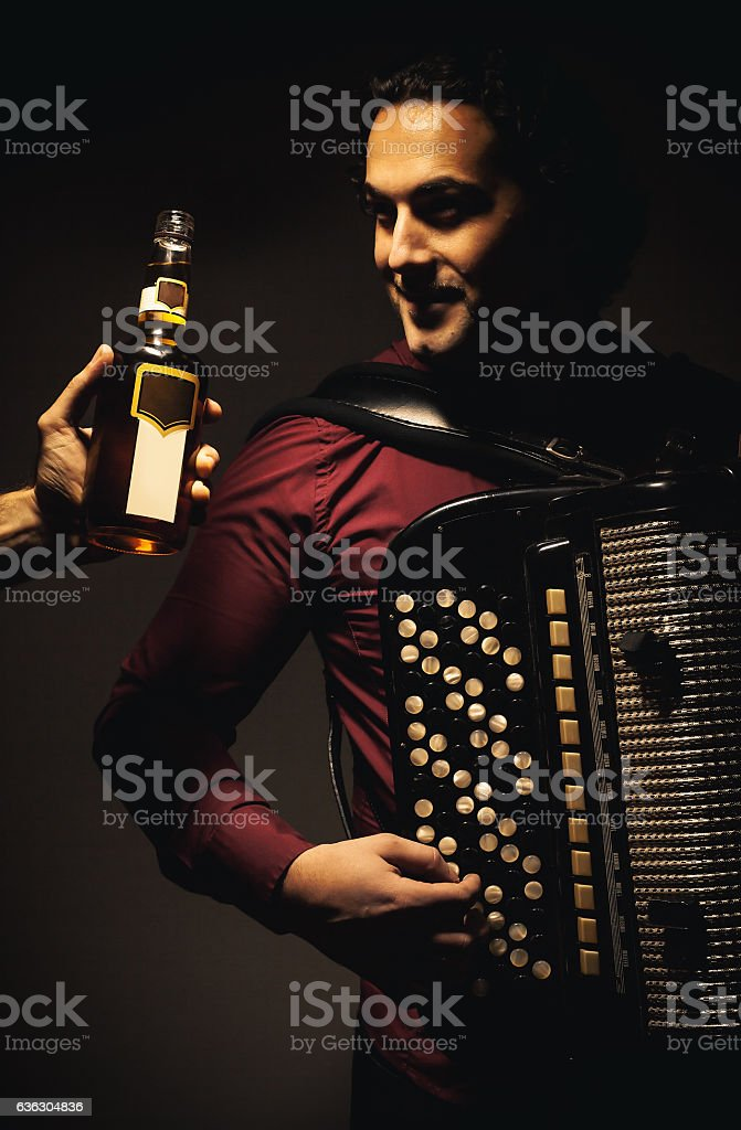 Chromatic Accordion Player And Bottle of Spirit Drink stock photo