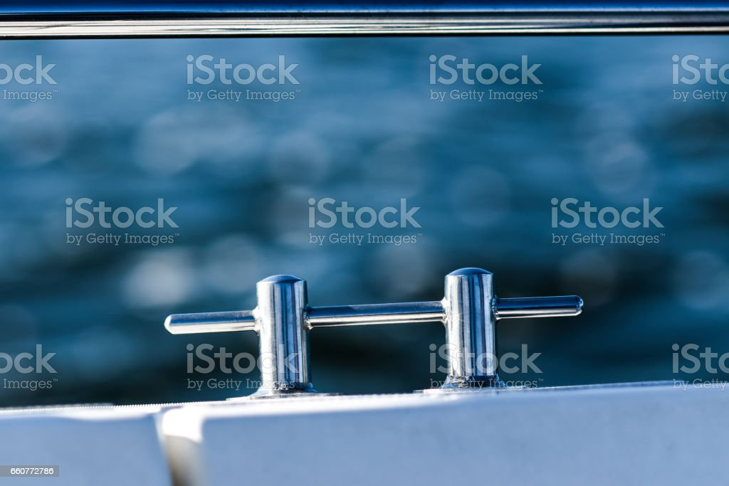 Chrome cleat on a white sailboat by the sea. stock photo