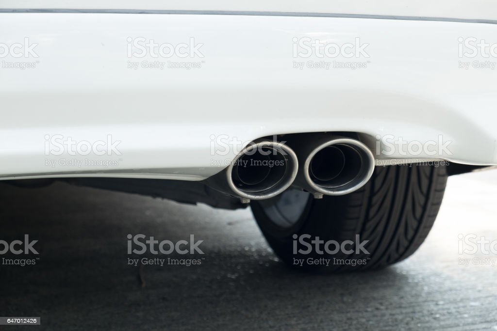Chrome exhaust pipe of white powerful sport car bumper stock photo