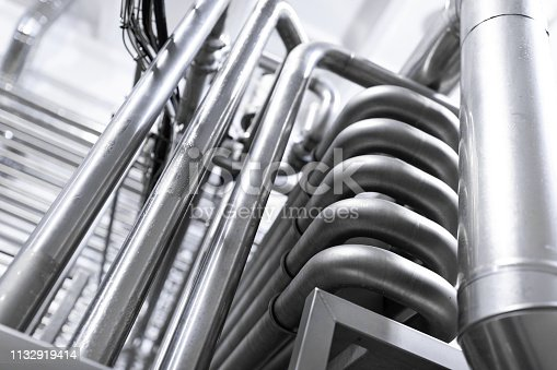 1132919442istockphoto Chrome pipes close-up. Industrial background 1132919414
