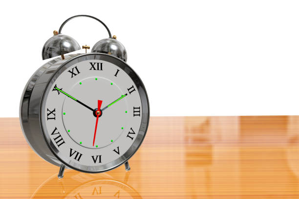 c565038ad62a Chrome twin bell alarm clock on a reflective wood surface and a white  background stock photo