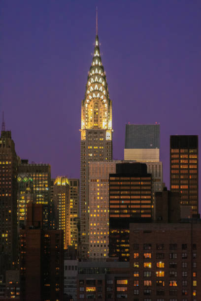 chrysler building illuminated at sunset, new york city skyline with midtown manhattan skyscrapers and clear sky. - chrysler building stock photos and pictures