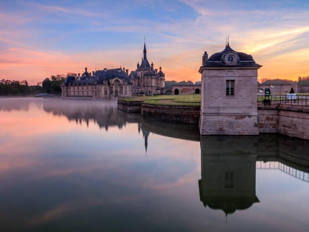 Château de chantilly au lever de soleil Aurore sur le château de Chantilly avec les couleurs du lever de soleil. Photo prise de l'extérieur du château depuis la route le juxtant picardy stock pictures, royalty-free photos & images
