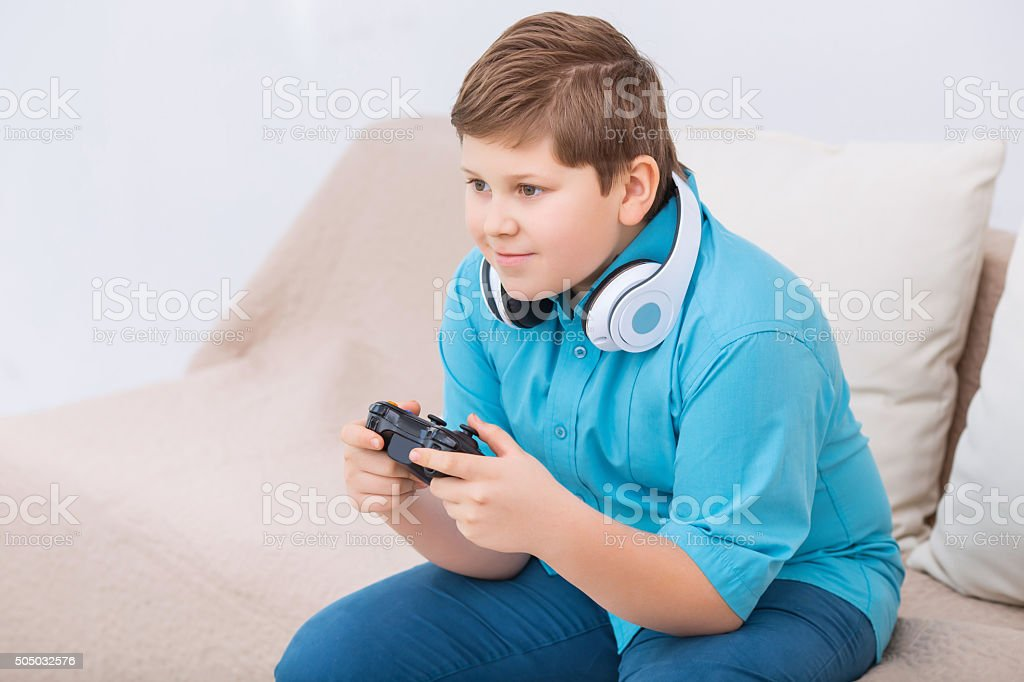 Chubby kid is playing video games stock photo