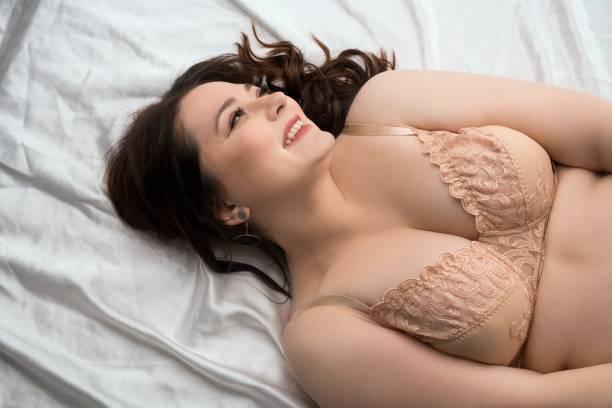 ベッドの上のランジェリーでブルネットを笑うぽっちゃり - real bodies ストックフォトと画像