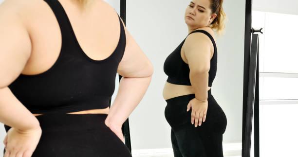mollige vrouw staan en kijken naar haar maag in een spiegel. - lichaamsbewustzijn stockfoto's en -beelden