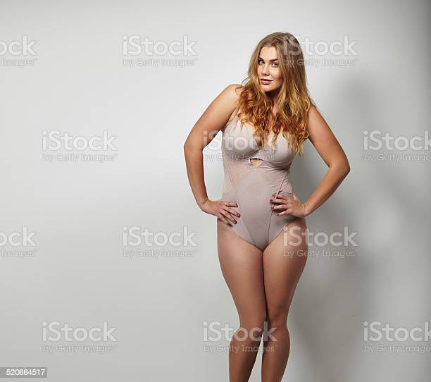 Chubby young woman in body stockings standing on grey background with her hands on hips looking at camera. Caucasian plus size female model in lingerie with copy space.