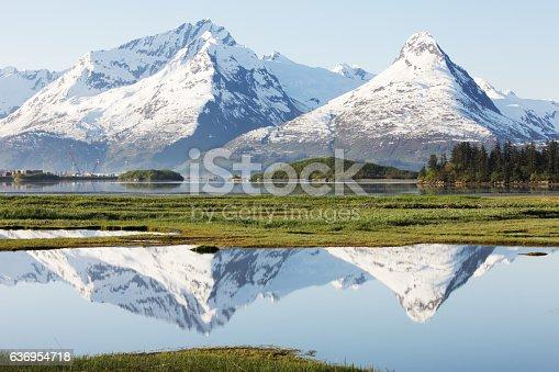 Chugach Mountains surrounding Valdez, Alaska reflect in foreground ponds inside Prince William Sound.