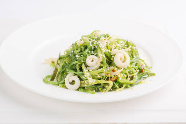 chuka seaweed salad with seafood and sesame seeds on a white plate stock photo