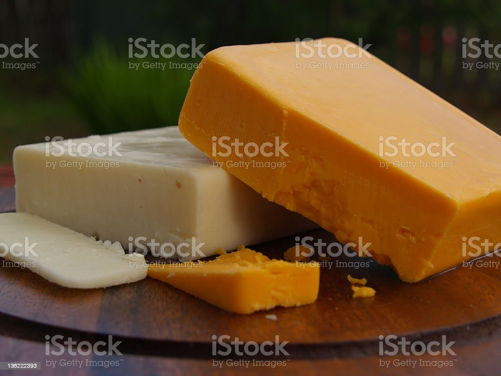 Chunks of cheddar cheese on plate stock photo