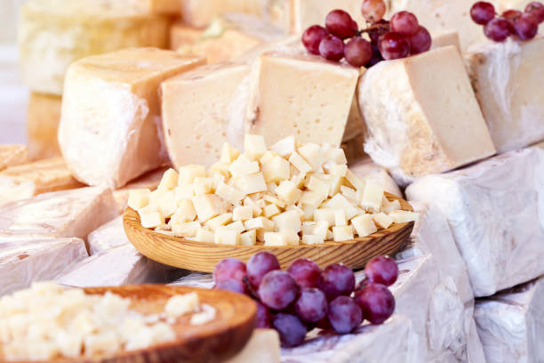 Chunks of cheese served on a wooden plate next to some red grapes stock photo