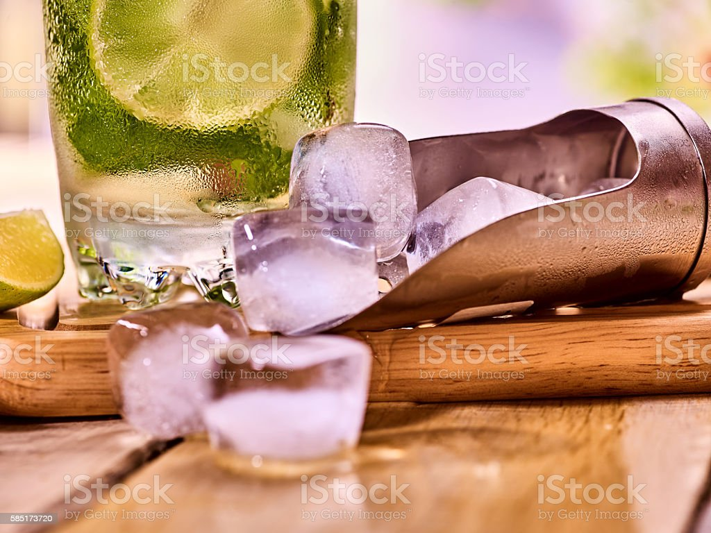 Chunks of ice cubes alcohol drink background on wooden boards. stock photo