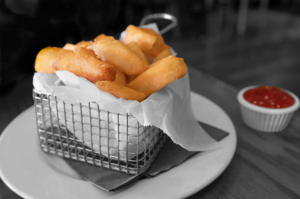 Chunky gourmet fries or chips in a square metal basket and a small tub of ketchup in selective colour with a monochrome background stock photo