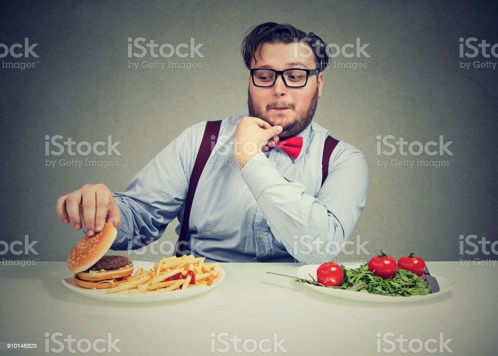 Chunky man craving delicious burger stock photo