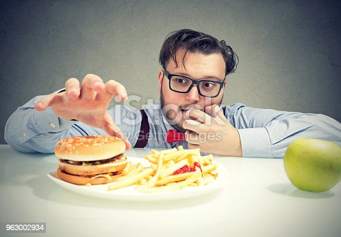 istock Chunky man craving for fast food 963002934