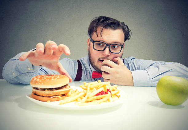 Chunky man craving for fast food Young obese man in glasses having cravings for cheeseburger with fries instead of healthy green apple. temptation stock pictures, royalty-free photos & images