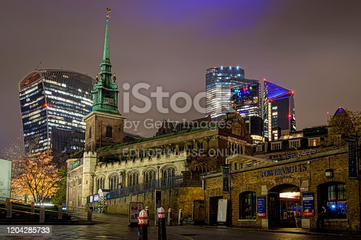 Church All Hallows by the Tower and the Skyscrapers of City of London on a cloudy, rainy evening. Man sitting in the entrance of a ticket shop.