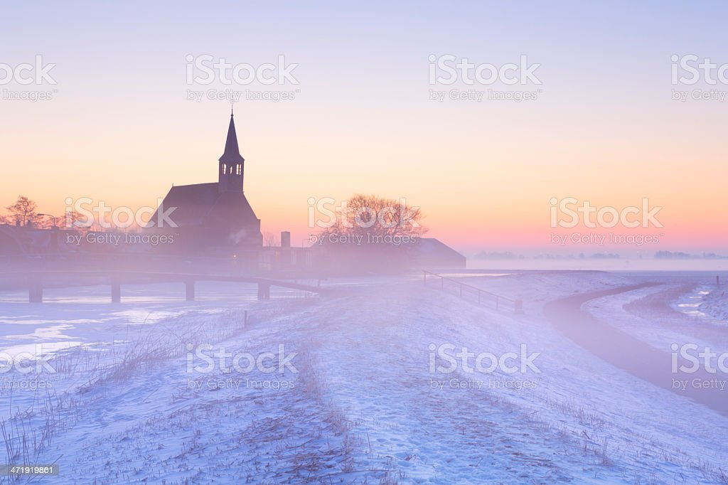 Church and canal in winter at sunrise, Oudendijk, The Netherlands stock photo