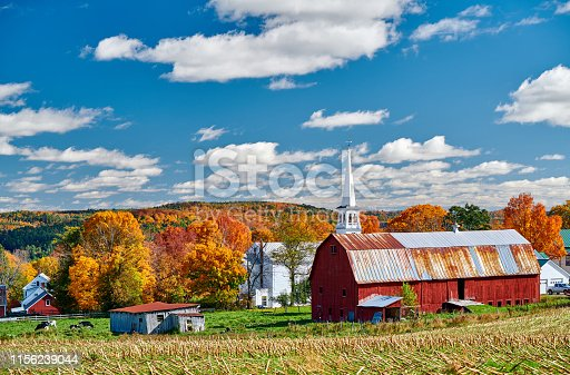 488912426istockphoto Church and farm with red barn at autumn 1156239044