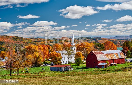 488912426istockphoto Church and farm with red barn at autumn 1156239047