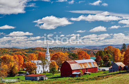 488912426istockphoto Church and farm with red barn at autumn 1156239051