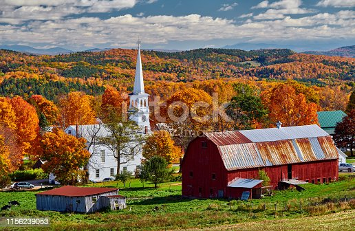 488912426istockphoto Church and farm with red barn at autumn 1156239053